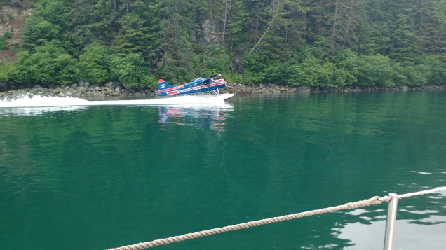 Seaplane landing next to boat entering Elfin Cove .Photo Ray Penson