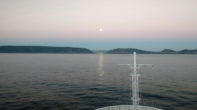 Moonset ahead and sunrise astern entering St Johns